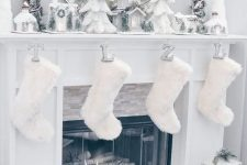 21 a winter wonderland mantel with mini Christmas trees, mini houses, candles, faux fur stockings and lanterns around