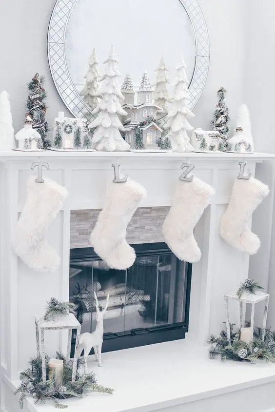 a winter wonderland mantel with mini Christmas trees, mini houses, candles, faux fur stockings and lanterns around