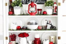 21 gorgeous Christmas decor with red lanterns and a candleholder, red blooms, faux greenery in pots and red ornaments