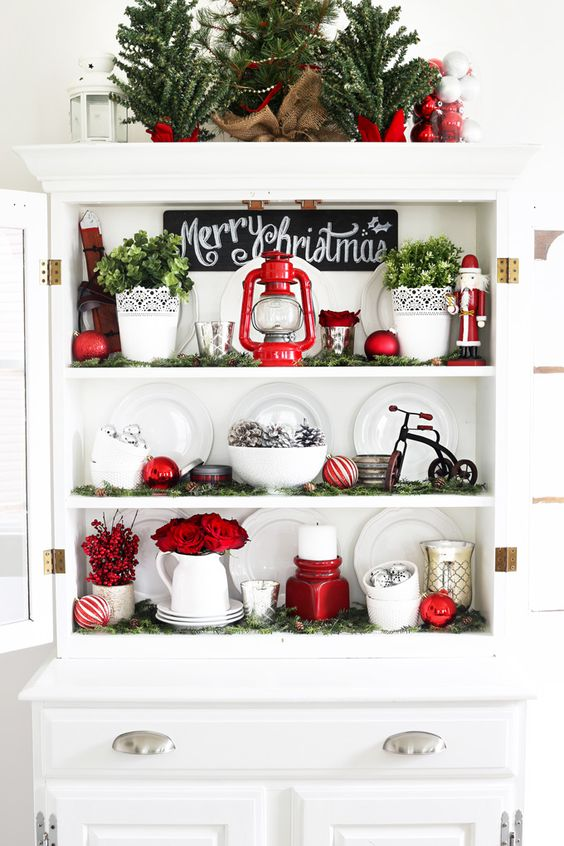 gorgeous Christmas decor with red lanterns and a candleholder, red blooms, faux greenery in pots and red ornaments