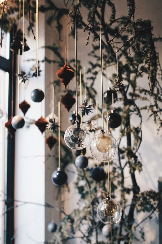 Christmas window decor done with fir branches and some chic sheer and colored ornaments hanging down