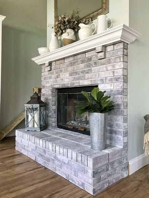 a farmhouse whitewashed brick fireplace with a white mantel, greenery in a bucket, a candle lantern for a cozy feel