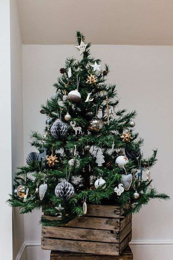 a pretty and bold Christmas tree with various ornaments of glass, felt, wood put into an old crate for a slight rustic touch