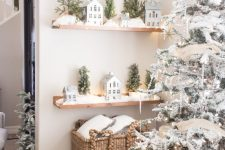 22 a winter wonderland nook with a flocked Christmas tree with lights, icicles, stars, open shelves with winter scenes is pure love