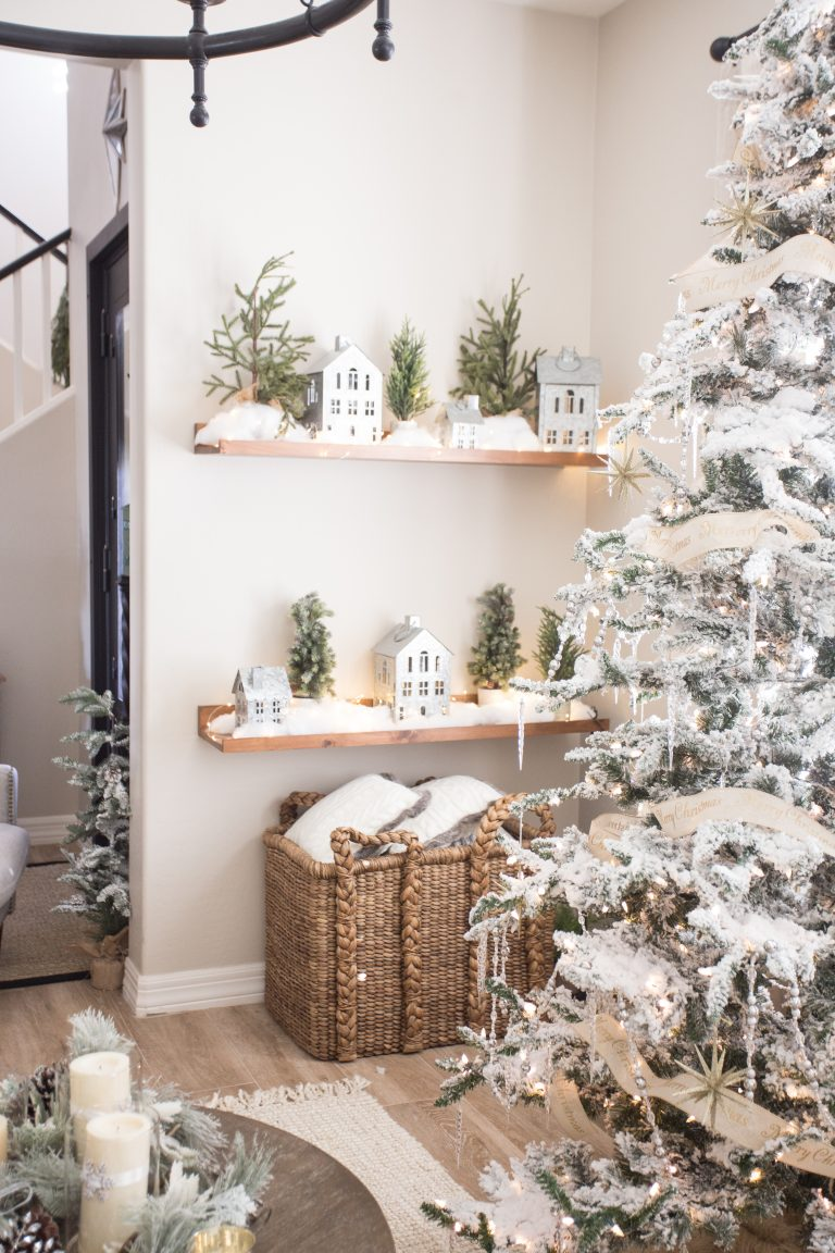 a winter wonderland nook with a flocked Christmas tree with lights, icicles, stars, open shelves with winter scenes is pure love