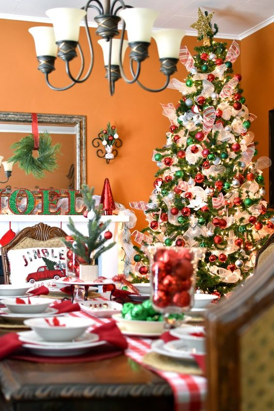 red and green Christmas tree decor with white ribbons and lights, plaid runners, red and green ornaments and bells on the table