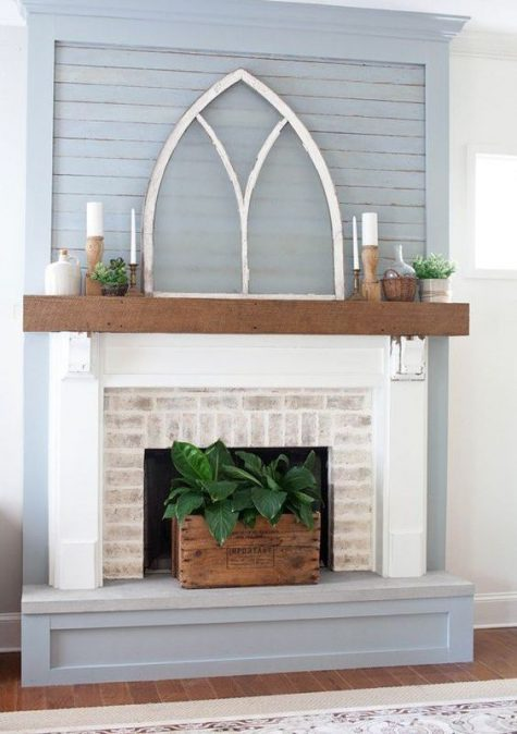 a farmhouse fireplace of whitewashed brick, a wooden mantel and light grey surround plus greenery