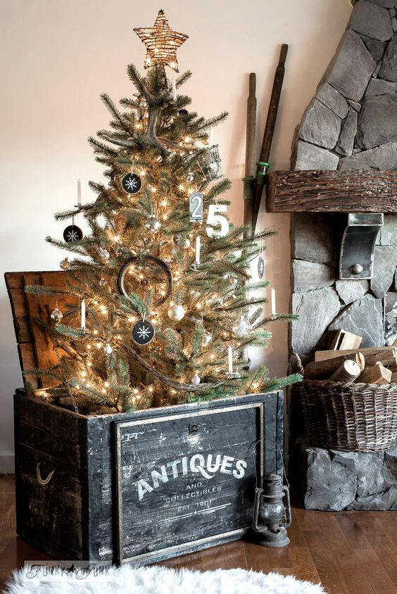 a rustic Christmas tree with lights, chalkboard ornaments, numbers, a stick star placed into a black chest is a cozy and cool idea