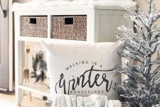 23 a winter wonderland nook with a mini flocked tree, a pillow and a knit blanket, mini trees and houses on the console table