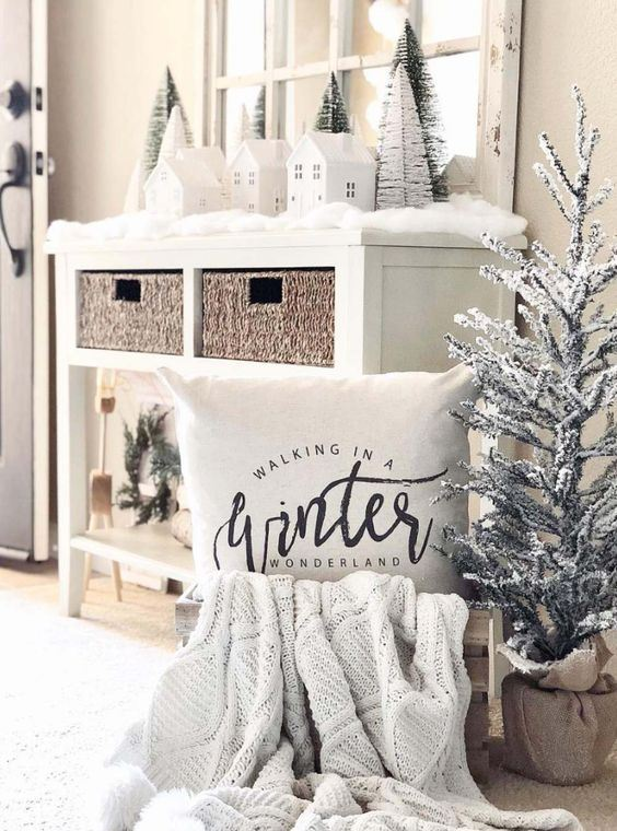 a winter wonderland nook with a mini flocked tree, a pillow and a knit blanket, mini trees and houses on the console table