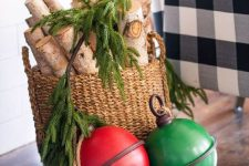 23 rustic Christmas decor with a basket with branches and fir branches and oversized red and green bells right on the floor