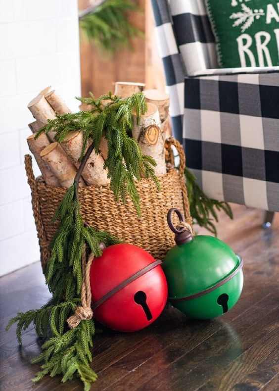 rustic Christmas decor with a basket with branches and fir branches and oversized red and green bells right on the floor