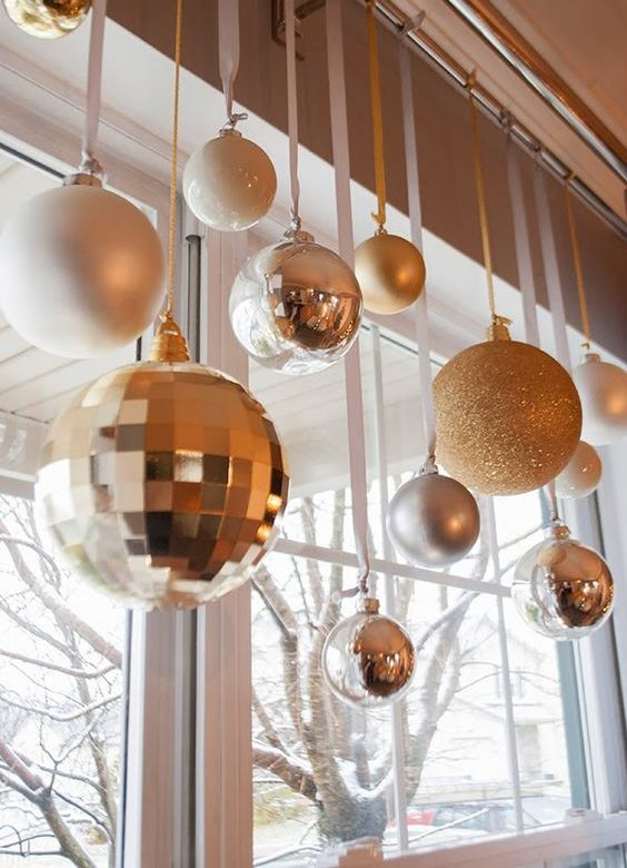 white, gold and silver Christmas ornaments of various sizes hanging on the window for chic holiday decor
