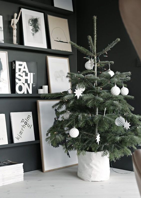 a Scandinavian Christmas tree with white and sheer ornaments and in a white fabric tree base collar looks very laconic and very stylish