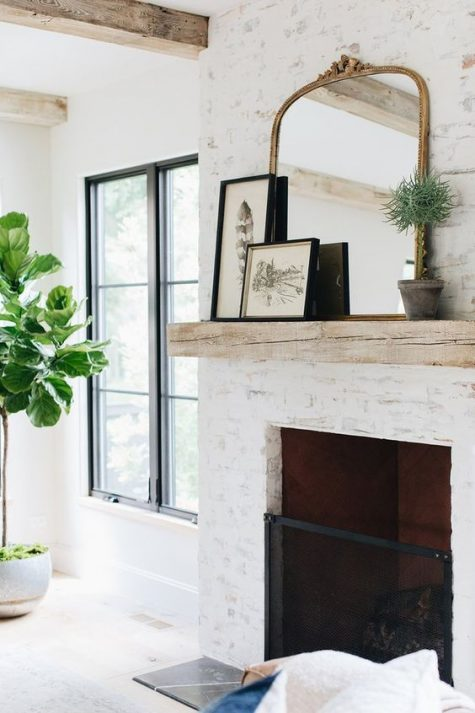 a chic whitewashed fireplace of brick and wiht a metal screen, a wooden mantel with artworks and a chic mirror