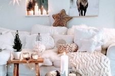24 an amazing winter wonderland living room with a white sectional, pillows and chunky knit, mini trees, candles, lots of stars and lights