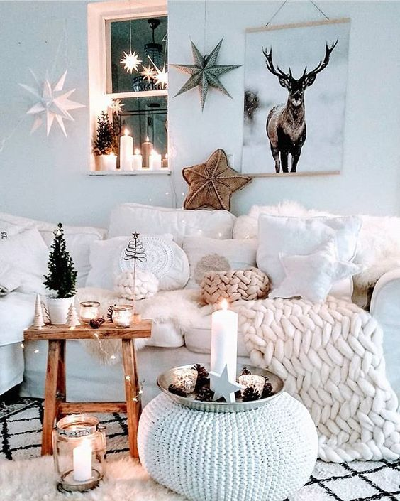 an amazing winter wonderland living room with a white sectional, pillows and chunky knit, mini trees, candles, lots of stars and lights