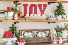 24 rustic red and green Christmas decor with wooden letters, lanterns, potted mini trees, painted pillows and plaid plates and vintage signs