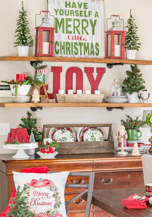 rustic red and green Christmas decor with wooden letters, lanterns, potted mini trees, painted pillows and plaid plates and vintage signs