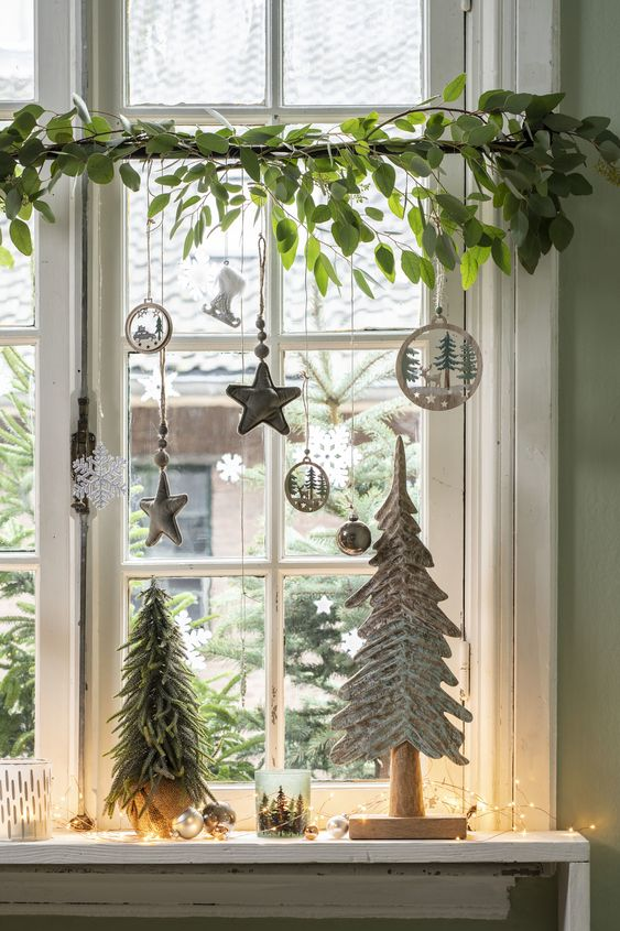 window Christmas decor with fresh greenery, silver and white ornaments, pretty wooden ornaments and mini trees