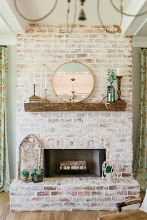 a beautiful whitewashed red brick fireplace with a rough wooden mantel, candles, greenery and a round mirror