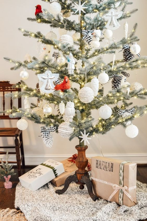 a vintage rustic Christmas tree with white and plaid ornaments and pinecones placed into a vintage wooden candleholder is a cool idea