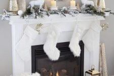 25 chic winter wonderland Christmas decor with white stockings, a flocked fir garland, candles, white deer, metallic trees on the mantel