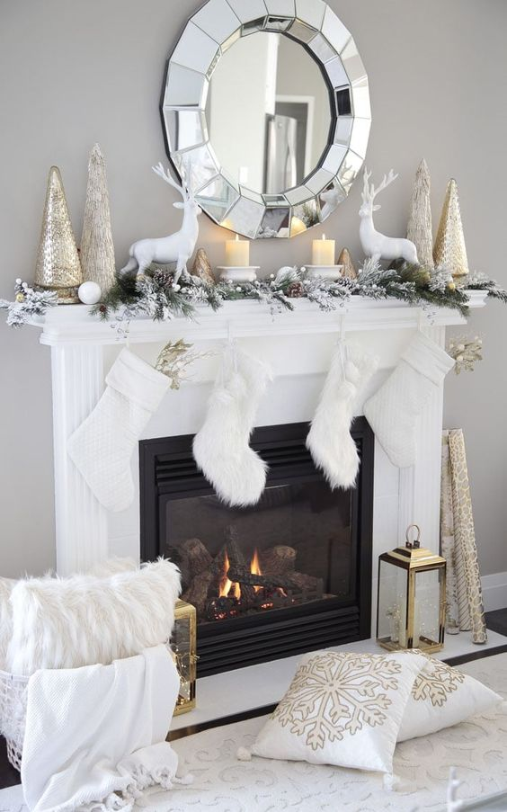 chic winter wonderland Christmas decor with white stockings, a flocked fir garland, candles, white deer, metallic trees on the mantel