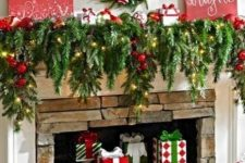 25 vintage bold red and green Christmas decor with fir branches, lights, red ornaments, a bright ornament wreath, red signs and faux gifts in the fireplace