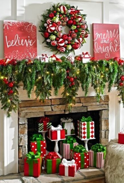 vintage bold red and green Christmas decor with fir branches, lights, red ornaments, a bright ornament wreath, red signs and faux gifts in the fireplace