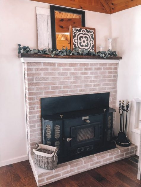 a beautiful whitewashed brick fireplace with a metal hearth, a walnut mantel and some greenery