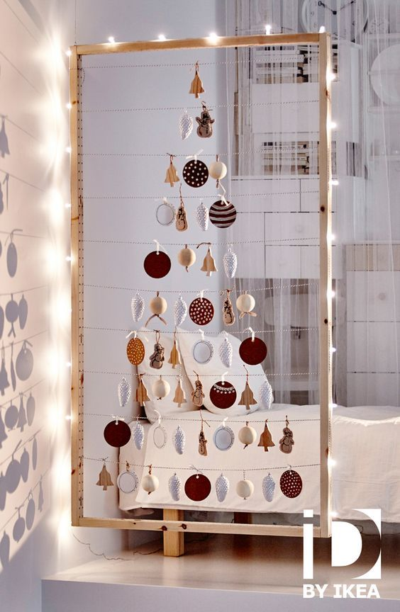 a frame with yarn and Christmas ornaments hanging on it and forming a tree, with lights on the perimeter