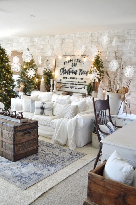 clusters of Christmas trees with lights, lots of paper snowflakes, lights, signs, branches and a white sofa with pillows for a winter wonderland feel