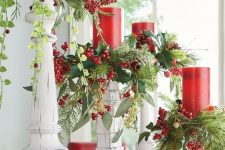 26 vintage Christmas decor done with white candleholders, greenery, red candles and berries is a lovely and refined idea with a rustic feel
