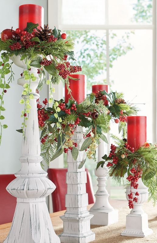 vintage Christmas decor done with white candleholders, greenery, red candles and berries is a lovely and refined idea with a rustic feel