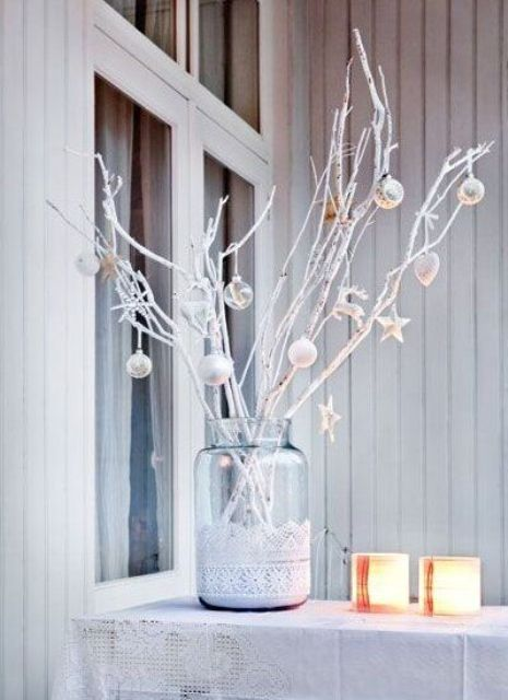 a large jar with white lace, whitewashed branches with white and silver ornaments is a chic decoration for Christmas