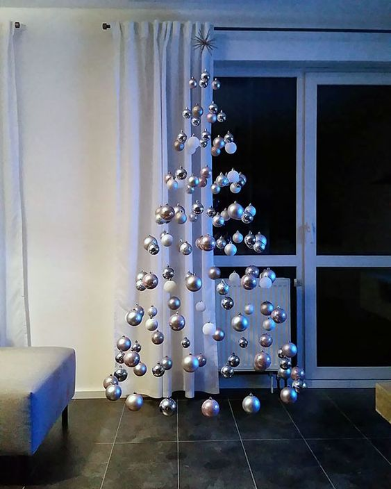 a levitating Christmas tree of white and silver ornaments is a lovely and out of the box idea for winter