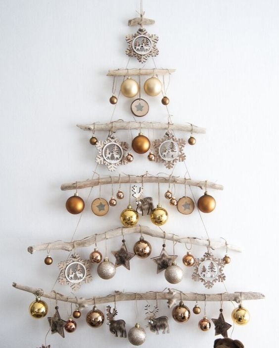 a wall-mounted Christmas tree of branches, gold and silver ornaments, wooden stars and snowflakes plus deer