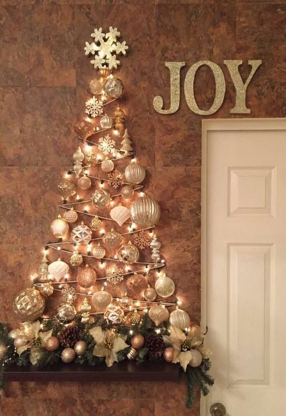 a wall-mounted Christmas tree of lights and white, copper and gold ornaments of various sizes and some pinecones and faux blooms