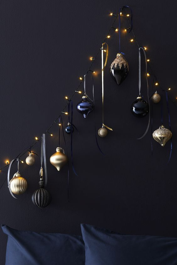 a wall-mounted Christmas tree of lights, with gold, black and navy ornaments is a chic and bold idea to rock anytime