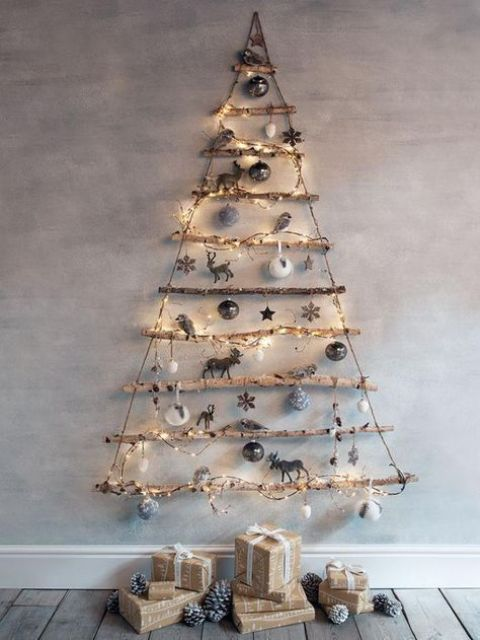 a wall-mounted stick Christmas tree with lights, silver and white ornaments is a lovely natural idea for winter holidays