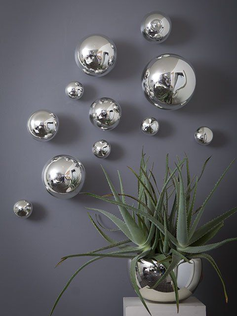 silver Christmas ornaments of various sizes attached to the wall bring a festive feel to the space but ina very modern way