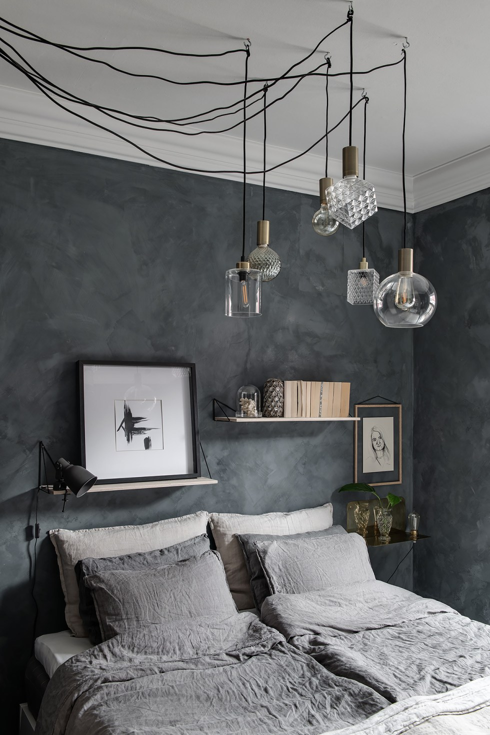 A Nordic bedroom with grey watercolor walls, a comfy bed and floating shelves and a nightstand plus a cool and catchy pendant lamps