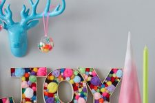 JOY letters filled with colorful pompoms are great for fun modern Christmas decor and you can make them yourself