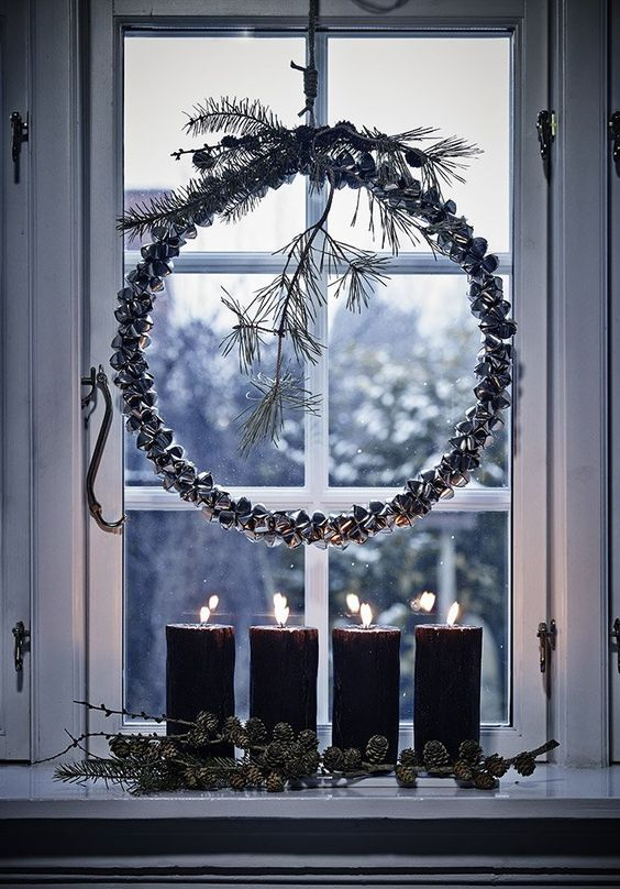 Nordic window decor with a bell wreath with twigs, pillar candles and pinecones looks amazing and very natural