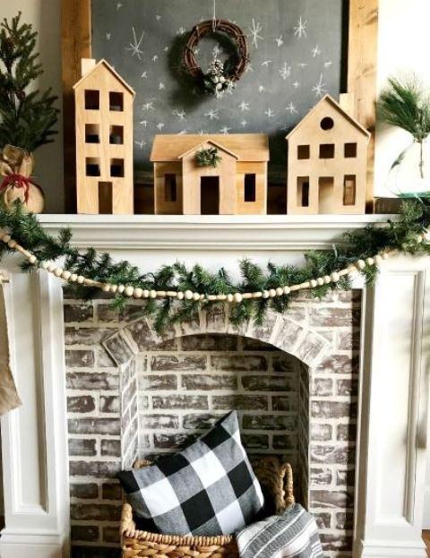 Scandinavian Christmas mantel decor with plywood houses, a fir garland, a wooden bead garland, a basket wiht plaid pillows