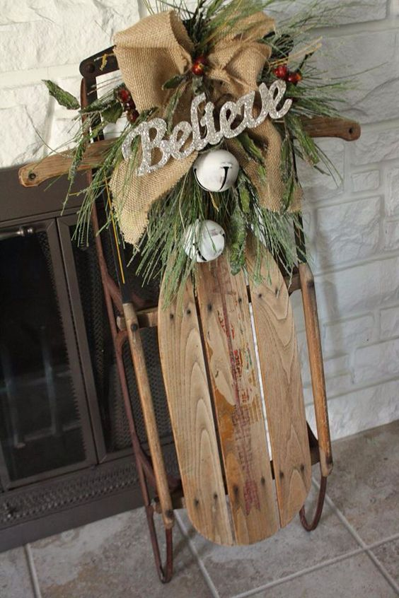 a Christmas decoration of a sleigh with a burlap bow, some berries, faux greenery and large white bells is a cozy vintage decor idea