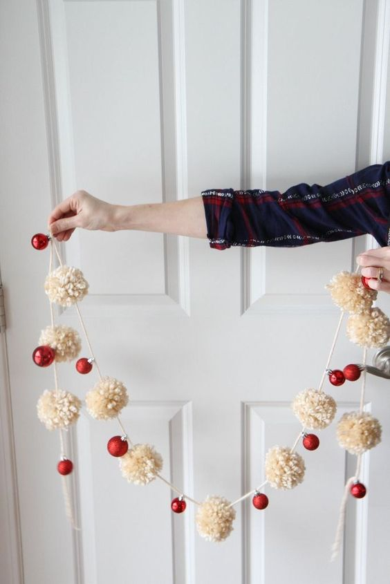 a Christmas garland of neutral pompoms and red ornaments is a truly holiday decoration to rock