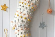 a Christmas stocking dotted wiht pastel pompoms is a cool decor idea for the holidays