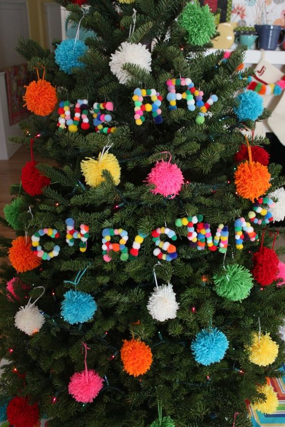 a Christmas tree with coloful pompom ornaments and colorful pompom letters is a lovely idea for the holidays